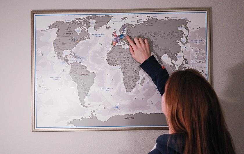 Mila (Symbolbild) zeigt auf Weltkarte.
