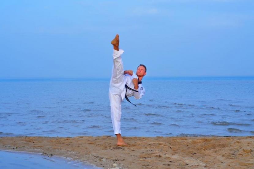 Taekwondo Großmeister mit hohem Halbkreisfußtritt am Strand