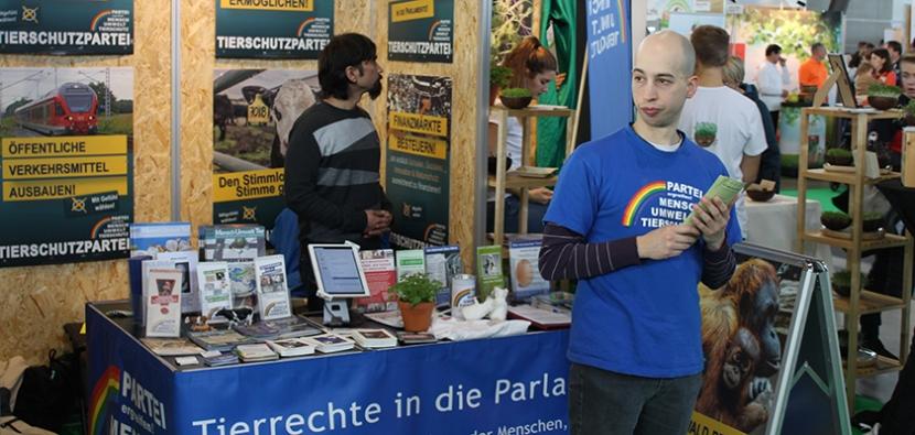 Mathias Gottfried von der Tierschutzpartei verteilt Flyer auf einer Messe.