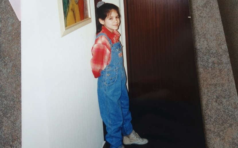 Foto von einem Bild, auf dem ein Mädchen in eienr Latzhose mit einem Zopf an einer Wand steht.