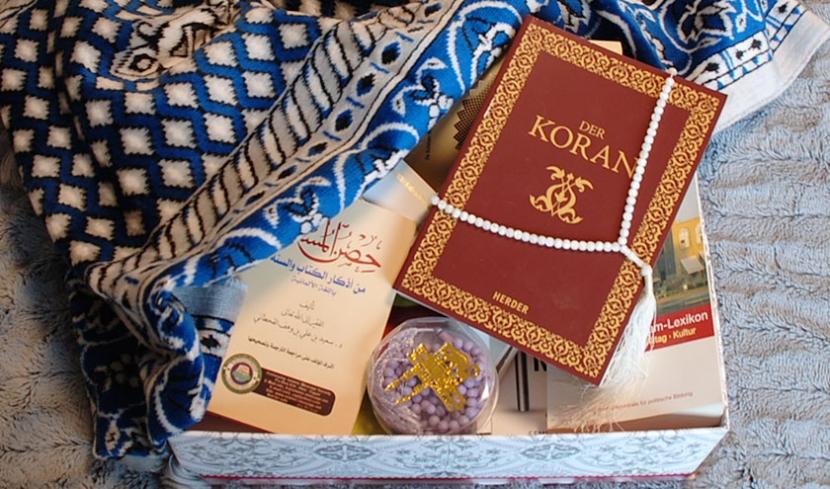 Box, gefüllt mit Büchern, Ketten und Teppich