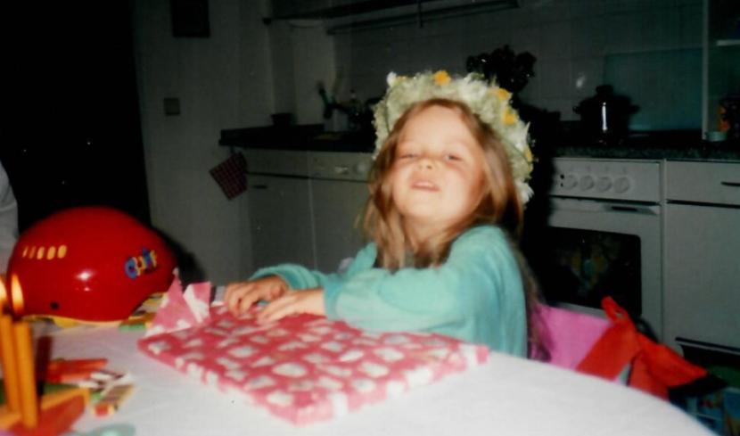 Ein kleines Mädchen sitzt am Küchentisch und packt Geschenke aus.
