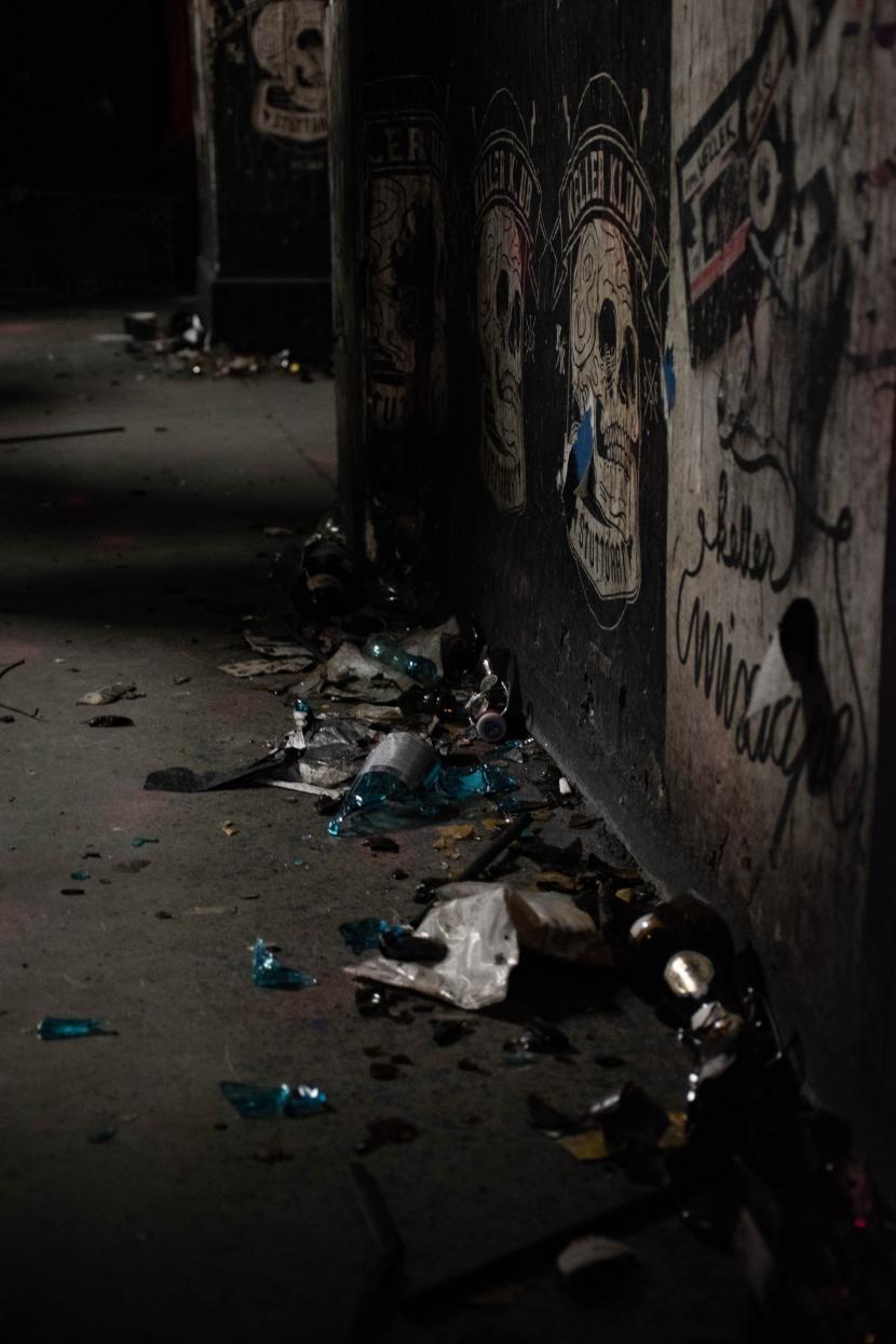 Auf dem Boden liegen Scherben vor einem Keller Klub Plakat