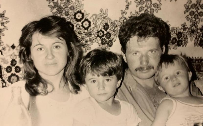Ehepaar mit zwei kleinen Söhnen vor einem Wandteppich.