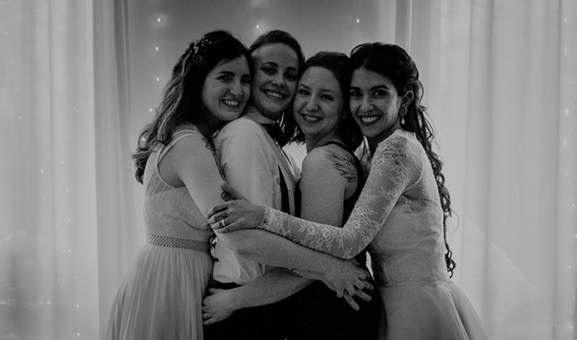 Vier Frauen umarmen sich.