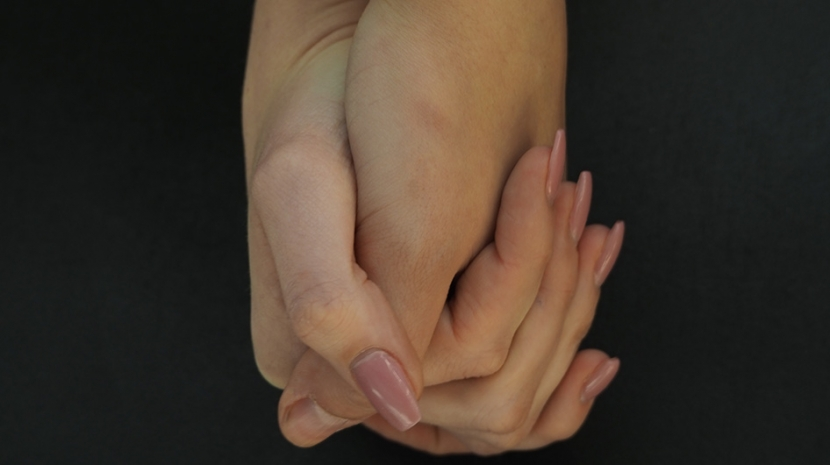 Zwei Hände, die sich aneinander festhalten.