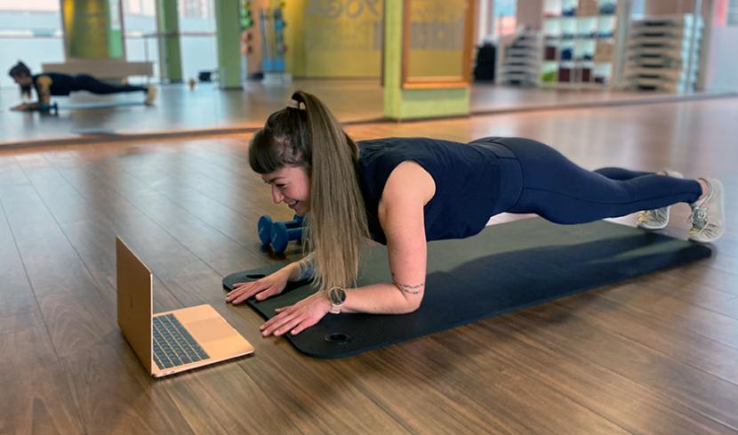 Eine junge Frau macht ein Home Workout vor dem Computer