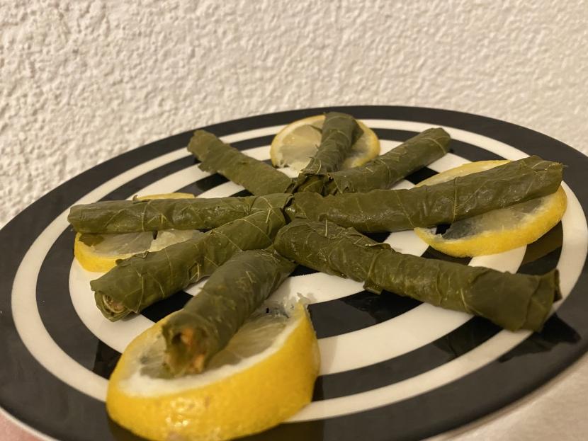 Ein Teller mit gefüllten Weinblättern und Zitronenscheiben