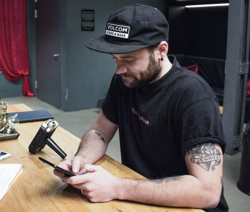 Julian sitzt am Handy und scrollt.