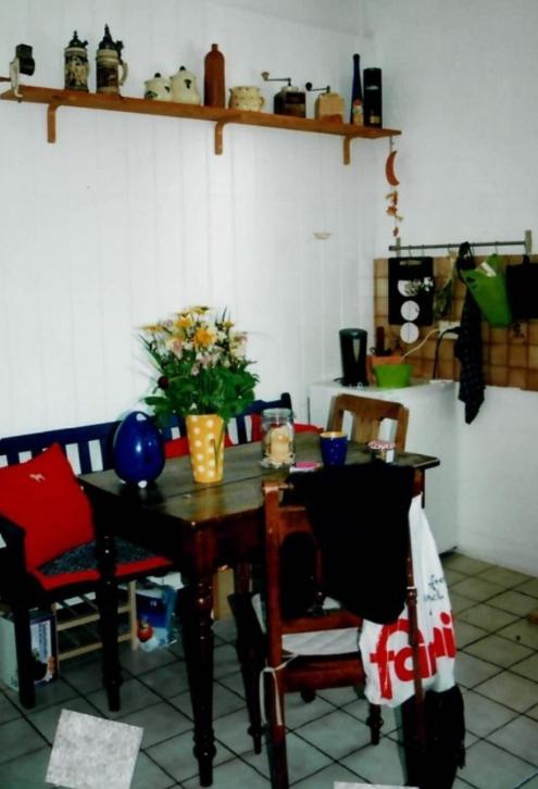 Ein Tisch in einer Küche, an den Stühlen hängen Jacken, an der Wand hängt ein Regalbrett.