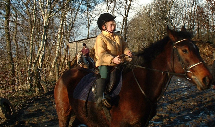 Nia reitet als kleines Kind auf einem Pferd