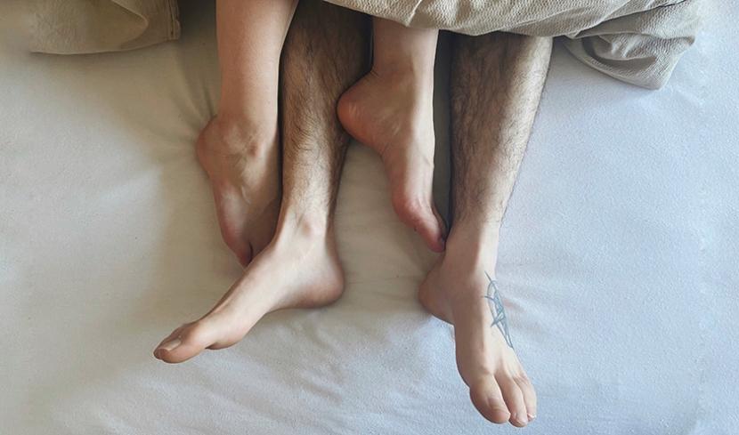 Zwei Paar Füße schauen unter einer Decke hervor.