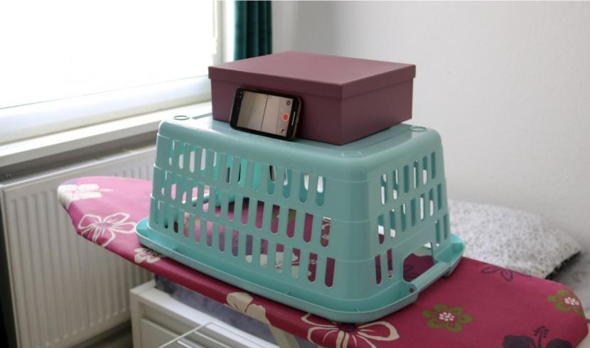 Auf einem pinken Bügelbrett steht ein türkiser umgedrehter Wäschekorb und auf diesem steht ein an eine violette Kiste angelehntes Smartphone.